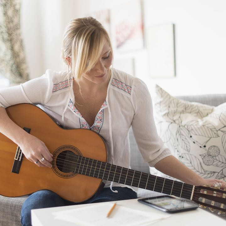 woman on couch writing song with guitar