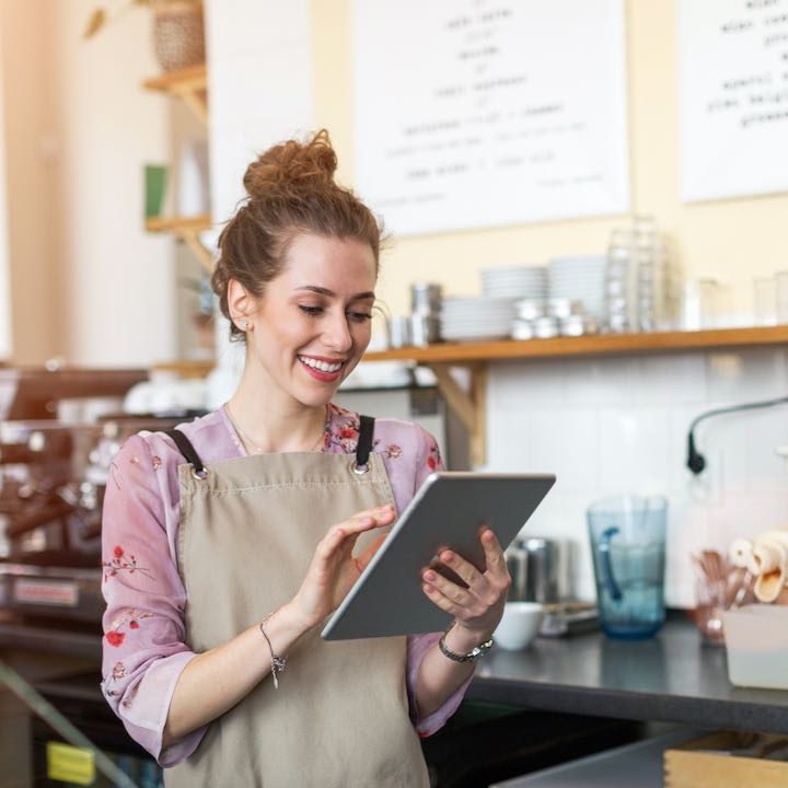 female business owner using tablet at bakery